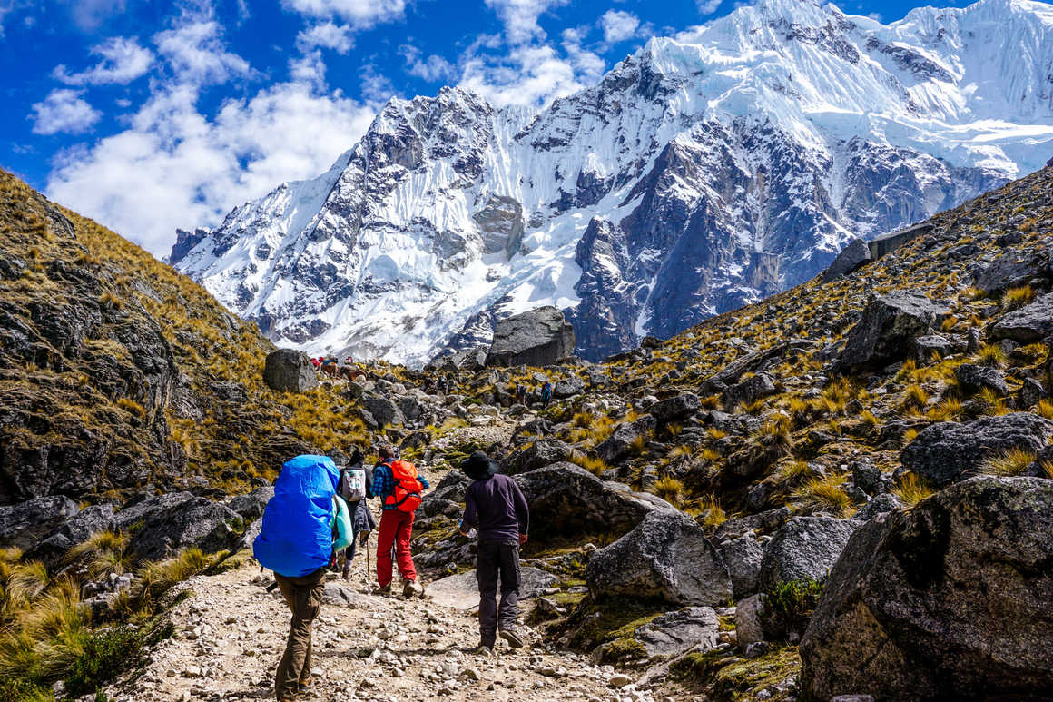 Hikers cimbing in front of the Salkantay glacier