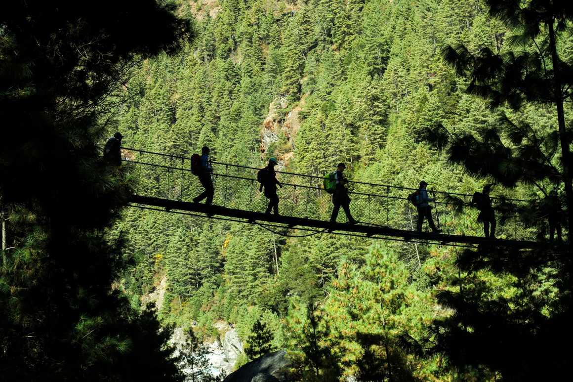 Hikers walking on suspended bridge in Padking, Nepal