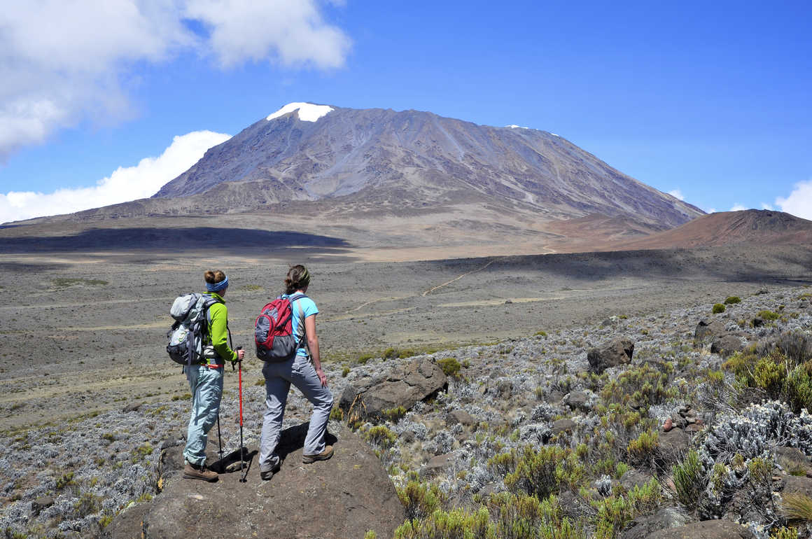 Two hikers looking at the Mount Kilimanjaro