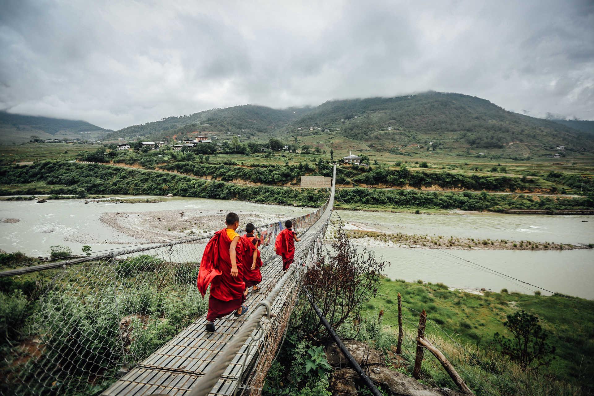 Young monks walking on a rope bridge in Bhutan