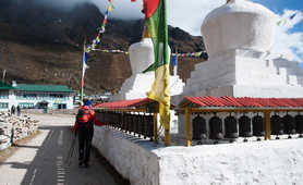 Hiker touching prayer wheels in the Everest region