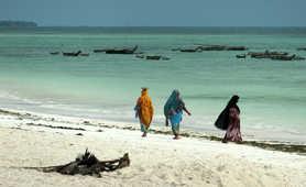 Local women walking on the beautiful beach of Zanzibar island