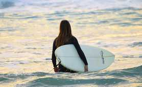 Surfing Woman With Surfboard Going To Surf In Ocean