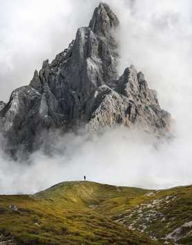 Trekker standing in front of steep mountain in the Dolomites