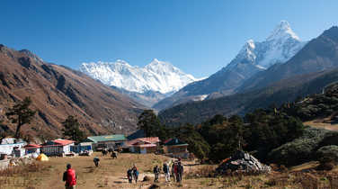 Hikers crossing a village in the Everest region