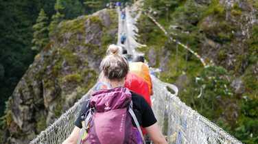 Hikers walking on rope bridge in Nepal