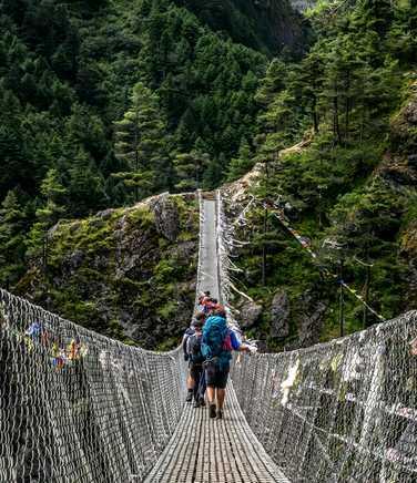 Hikers walking on rope bridge in the Everest region