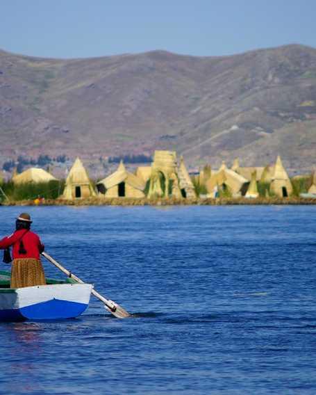 Peruvian woman navigating on Titicaca lake