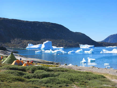 Camp on the coast of Greenland in front of icebergs