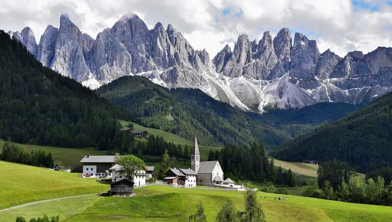Church in an alpine meadow surrounded by forest and mountains
