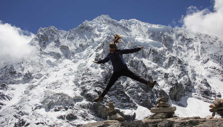 Hiker jumping in front of the Salkantay glacier