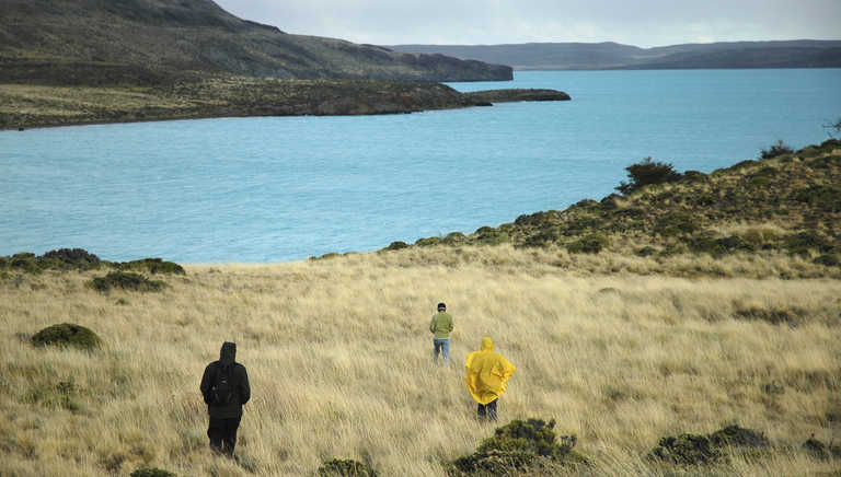 Hikers getting closer to a beautiful lake in Patagonia