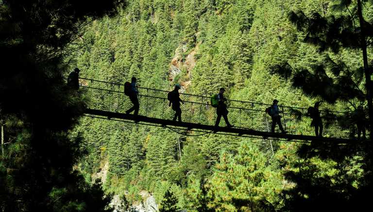 Hikers walking on suspended bridge in Padking, Nepal