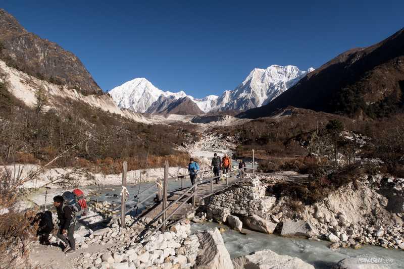 Hikers crossing a bridge during the Manaslu Circuit Trek